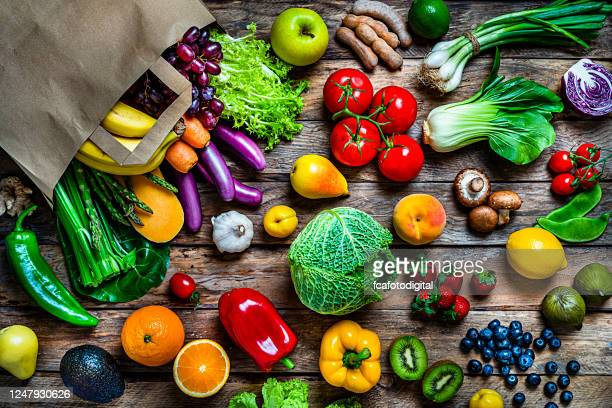 shopping bag filled with fresh organic fruits and vegetables shot from above on wooden table - fruit stock pictures, royalty-free photos & images