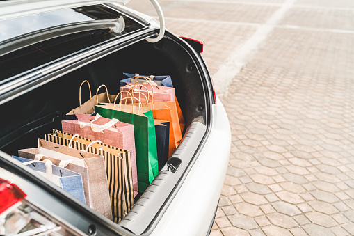 Shopping bags in car trunk with copy space. Modern shopping lifestyle, rish people or leisure activity concept 851903602