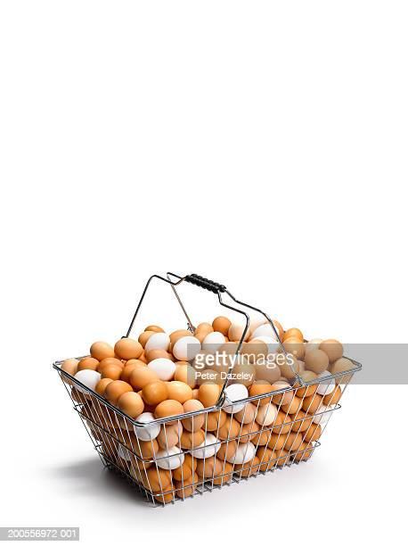 Shopping basket full of eggs on white background