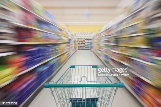 shopping cart amidst racks in supermarket - aisle stock pictures, royalty-free photos & images