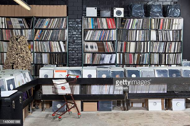 A shopping cart and rows of records on shelves and in bins at a record store
