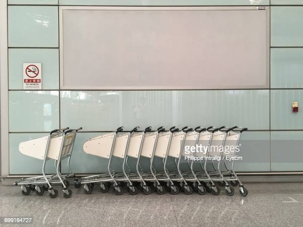 Shopping Cart Arranged On Tiled Floor By Wall In Mall