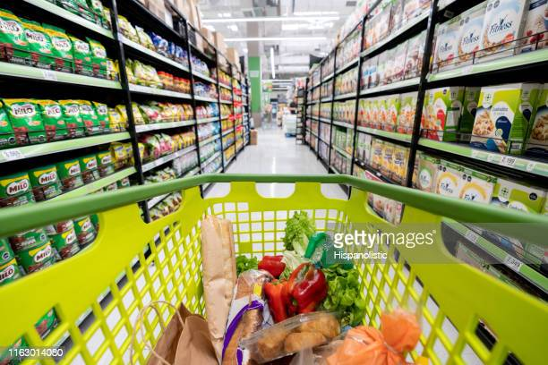 shopping cart down the supermarket aisle filled with groceries - shopping cart stock pictures, royalty-free photos & images