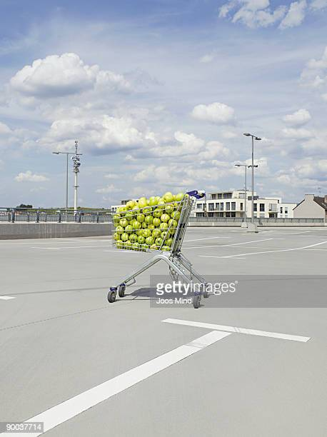shopping cart filled with apples on parking lot
