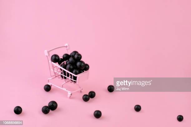 Shopping cart filled with black balls
