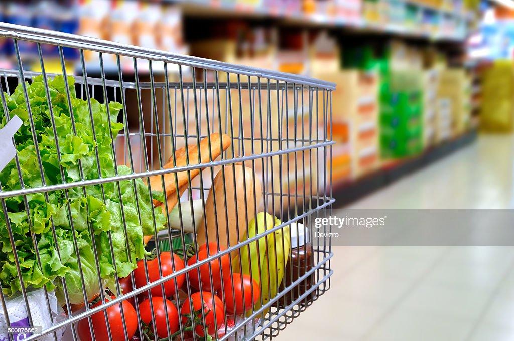 Shopping cart full of food in supermarket aisle side tilt : Stock Photo