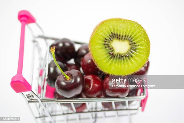Shopping cart full of fruit and cherries and kiwis