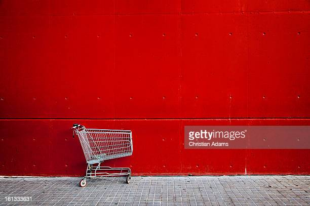 shopping cart in front of a red wall - abandoned stock pictures, royalty-free photos & images