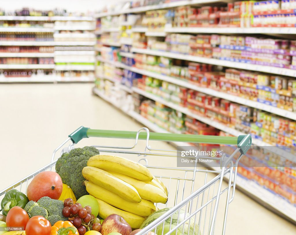 Shopping cart in grocery store full of fruits and vegetables : Stock Photo