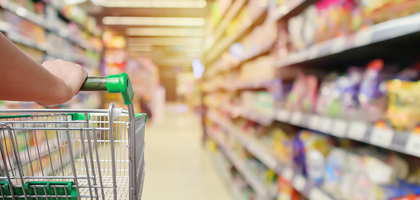 shopping cart in supermarket aisle with product shelves interior defocused blur background 1128949343