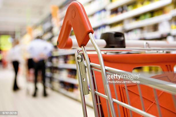 Shopping cart in supermarket, shoppers in background