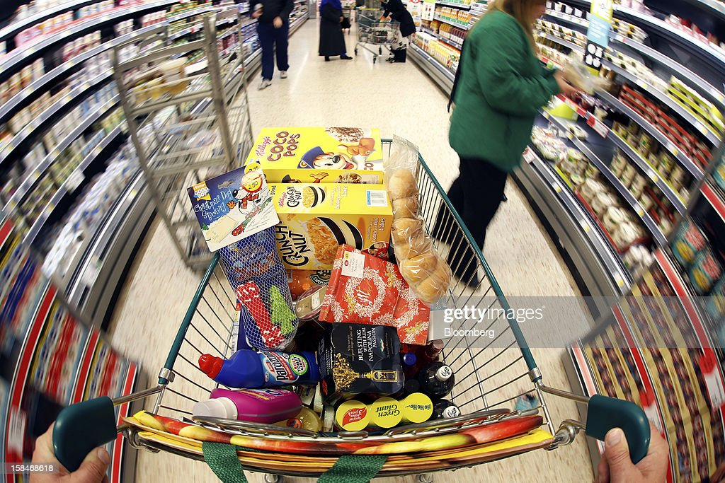 A shopping cart laden with groceries is pushed through the aisle in this arranged photograph at a Morrisons supermarket in Chadderton, U.K., on Monday, Dec. 17, 2012. The British Christmas is the biggest epicurean occasion of the year, with households spending a total of 4 billion pounds on food in the final week before Dec. 25. Photographer: Paul Thomas/Bloomberg via Getty Images