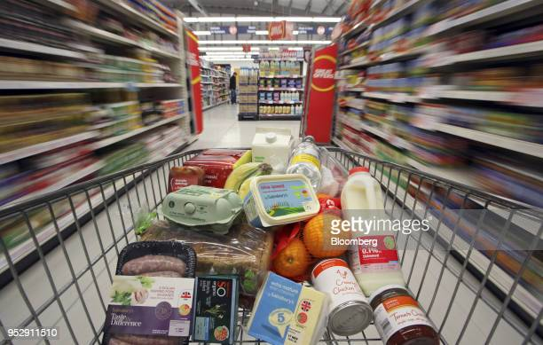 A shopping cart loaded with Sainsbury'sbranded produce is pushed through the company's supermarket in this arranged photograph in Stockport UK on...