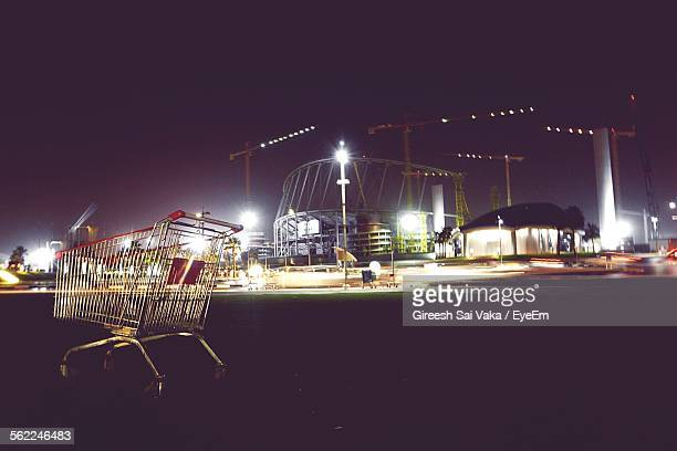 Shopping Cart On Field Against Illuminated Construction Site At Night