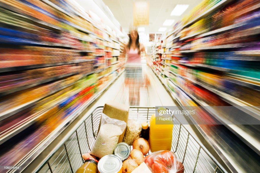 Shopping cart races through store with rainbow motion blur surrounding : Stockfoto