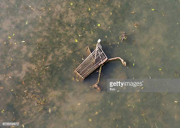 shopping cart, thrown away in a dirty river - symbol for minimalism and consumerism - capitalism stock pictures, royalty-free photos & images