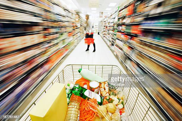 Shopping cart with rainbow motion blur along aisle of supermarket