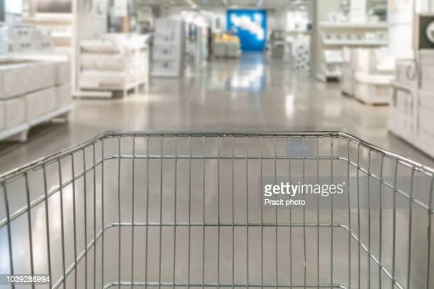 shopping cart with supermarket aisle blur abstract background - mercado espaço de venda no varejo - fotografias e filmes do acervo