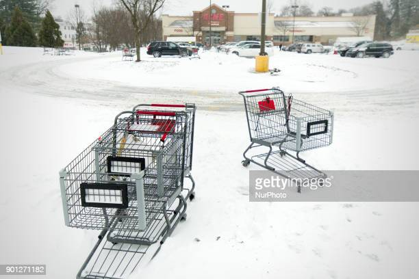 Shopping carts are left stranded in a snowbank at a grocery store parking lot as the region braces for the 'Bomb Cyclone' winter storm Grayson on...
