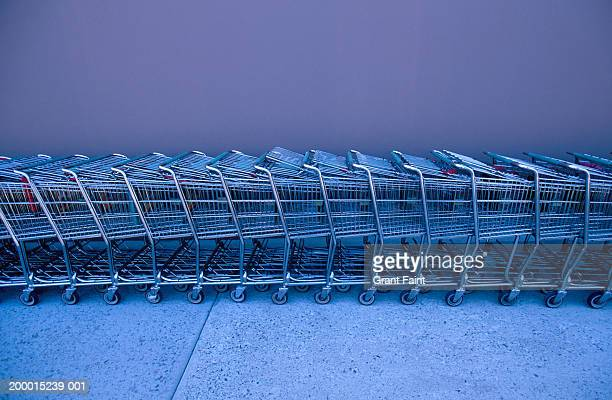 shopping carts lined up against wall - shopping cart stock pictures, royalty-free photos & images