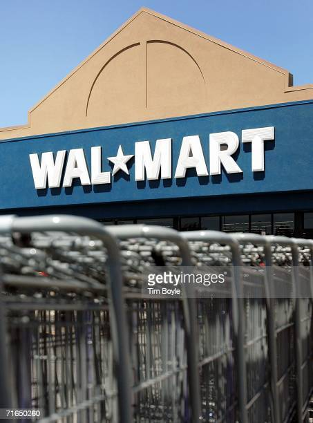 Shopping carts sit in a row outside a WalMart store August 15 2006 in Mount Prospect Illinois WalMart profits fell 26 percent for the quarter the...