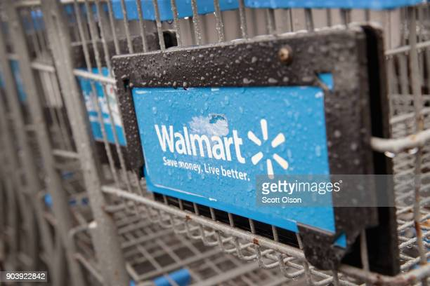 Shopping carts sit outside of a Walmart store on January 11 2018 in Chicago Illinois Walmart announced today it would use savings from the recently...