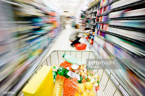Shopping cart's speed creates rainbow motion blur in supermarket aisle