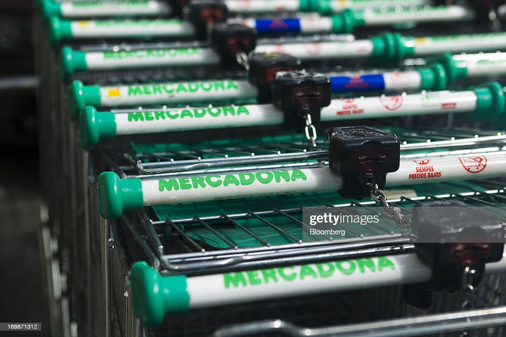 Shopping carts stand chained together before use outside a Mercadona supermarket in Madrid, Spain, on Thursday, May 16, 2014. Billionaires Juan Roig and Hortensia Herrero, the husband-and-wife team that controls Mercadona SA, Spain's largest supermarket chain, created thousands of jobs last year as their country's economy crumbled. Photographer: Angel Navarrete/Bloomberg via Getty Images