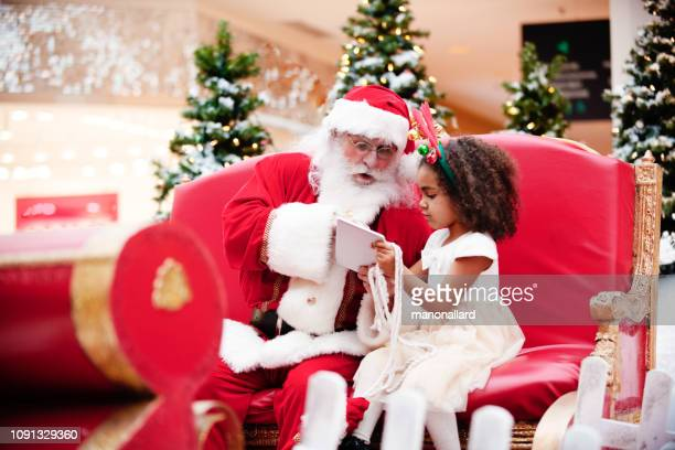 shopping christmas with family and santa claus at shopping mall - santa stock photos and pictures