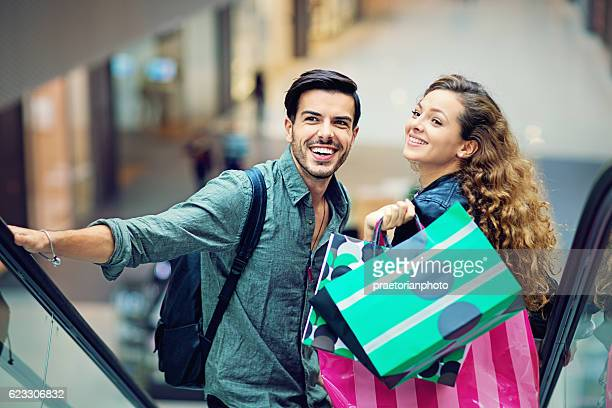 Shopping couple are laughing on the escalator in Mall