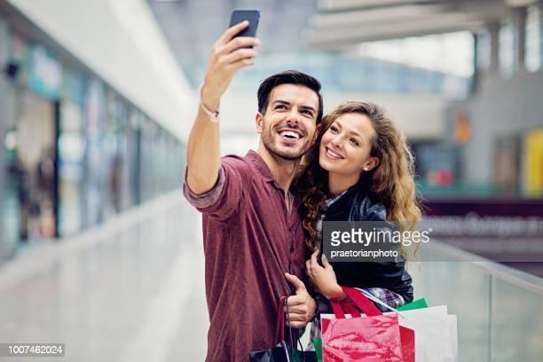 カップルをショッピング モールで selfie/メイキング ビデオ通話を取っています。