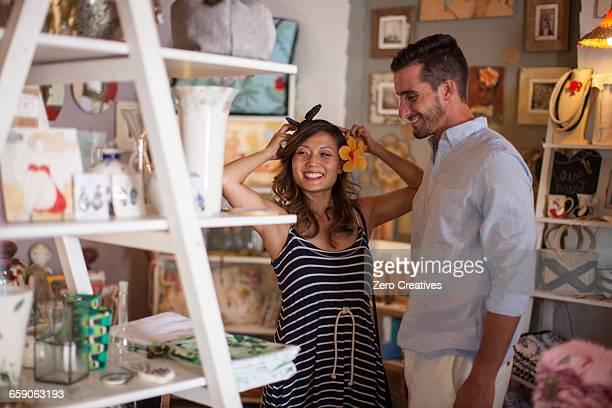 shopping couple trying on flower headdress in gift shop - ギフトショップ ストックフォトと画像
