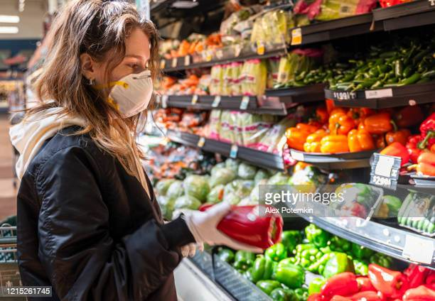 shopping during a pandemic. a young woman wearing protective mask and gloves shopping vegetable in a store. - alex potemkin coronavirus stock pictures, royalty-free photos & images