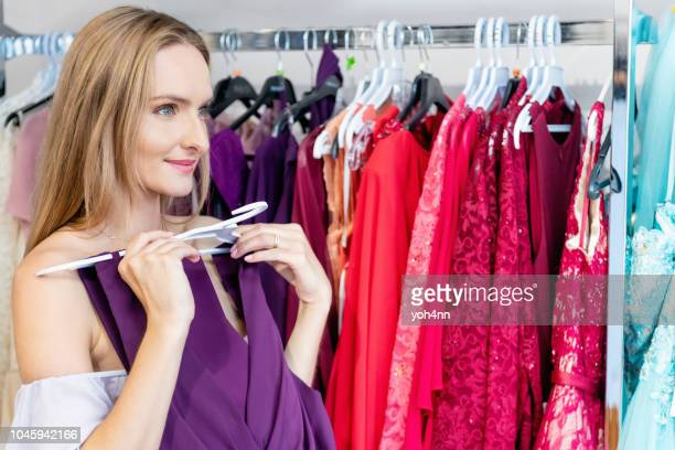shopping for evening wear - purple dress stock pictures, royalty-free photos & images