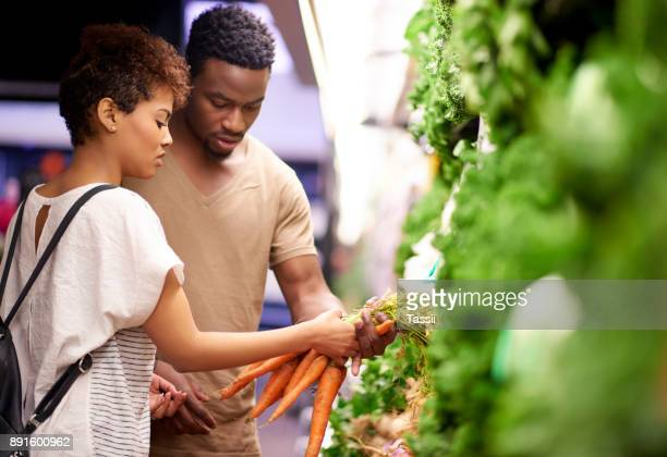 shopping for the freshest produce at the best price - produce aisle stock photos and pictures