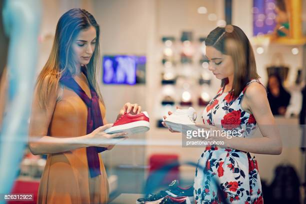 Shopping girlfriends are choosing shoes in a boutique and sulking each other after a conflict
