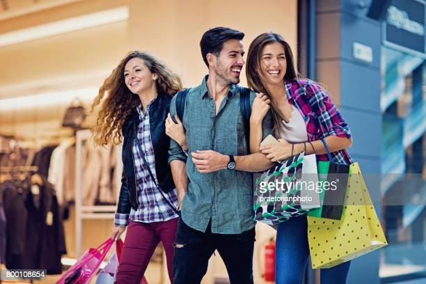 Compras meninas e homem estão andando no shopping
