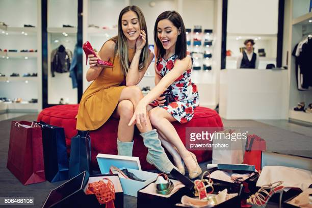 Shopping girls are choosing shoes in a boutique and make fun