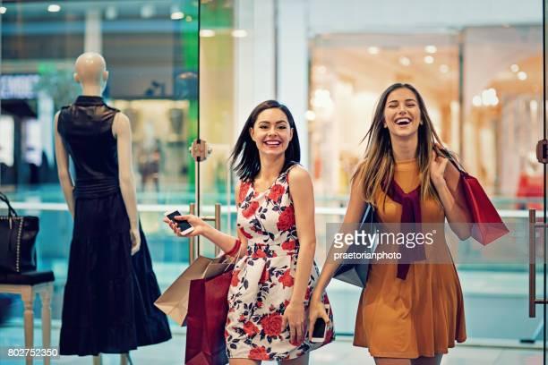 Shopping flickor går in i en kläder butik