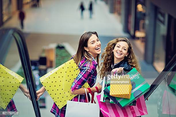 shopping girls are laughing on the escalator in mall - shopping stock pictures, royalty-free photos & images