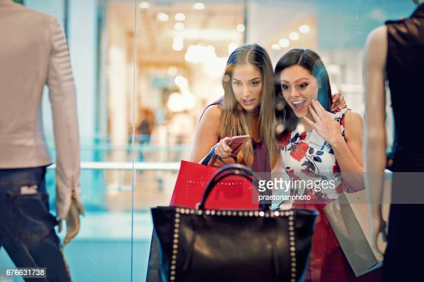 shopping girls are looking store window in the mall - consumentisme stockfoto's en -beelden