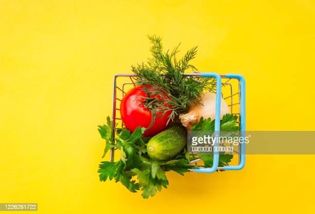 shopping grocery cart metal on yellow background. food basket concept close up. copy space. flat lay - vegetais - fotografias e filmes do acervo