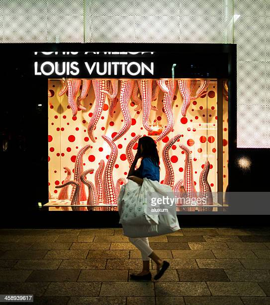shopping in ginza tokyo japan - louis vuitton designer label stock photos and pictures