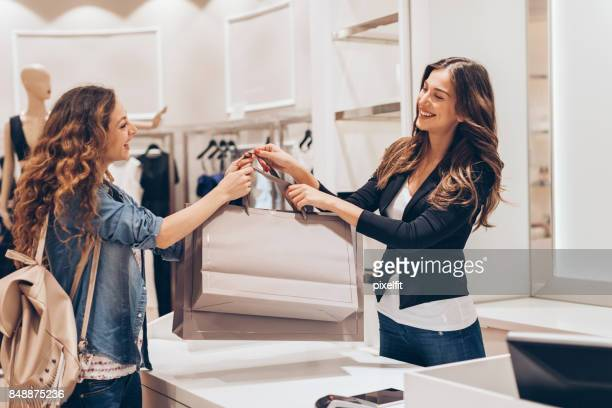 shopping in the fashion store - saleswoman stock photos and pictures