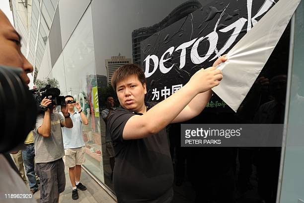 A shopping mall security guard takes down a poster saying 'detox' put up by members of the enviromental group Greenpeace as part of a protest at a...