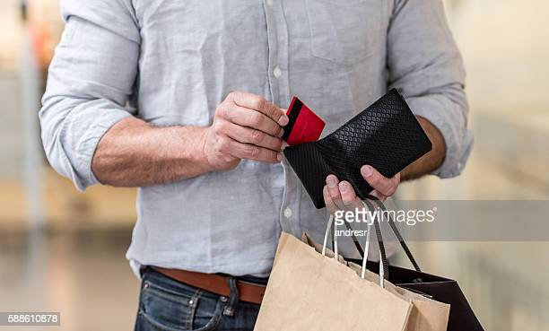 shopping man putting credit card in his wallet - spending money stock pictures, royalty-free photos & images