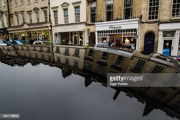 Shopping on a Sunday afternoon in Milsom Street, Bath. The roofs of the buildings are reflected in the roof of the car.