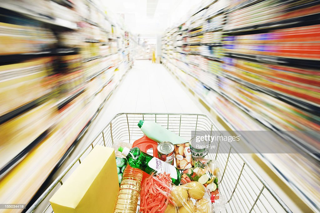 Shopping on the run! Speed seriously blurs supermarket shelves : Stock Photo
