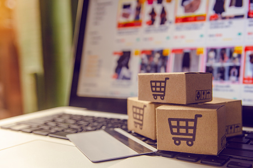 Shopping online concept - Shopping service on The online web. with payment by credit card and offers home delivery. parcel or Paper cartons with a shopping cart logo on a laptop keyboard 1133980246