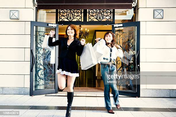 shopping spree: women rushing out luxury boutique - japanese short skirts stock photos and pictures